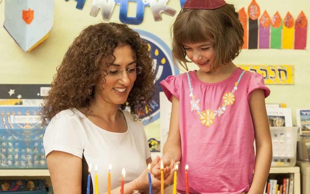 Kindergarten teacher Nirit Yakov lights a menorah with a student at Tehiyah Day School in California. Courtesy of Tehiyah Day School