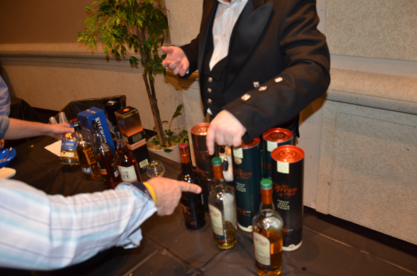 A Guys' Night Out attendee picks out his scotch from one of several tables