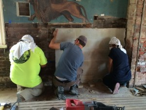Following a week of conservation, the original portions of the synagogue mural were removed from the wall and placed into storage crates.  Photo courtesy of The Jewish Historical Society