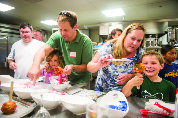 Apples for the New Year:  Rob Morse, left, and his daughter Victoria, 7, and Cindy Venick and her son, Michael, 7, make candied apples at the annual community-wide religious school kick off held Sunday at Temple Shalom in Chevy Chase. Other activities included a High Holidays crash course, a gaga kickball tournament, Yoga Shalom, Israeli dancing and a workshop called Stand Up for Israel.  Photo by David Stuck