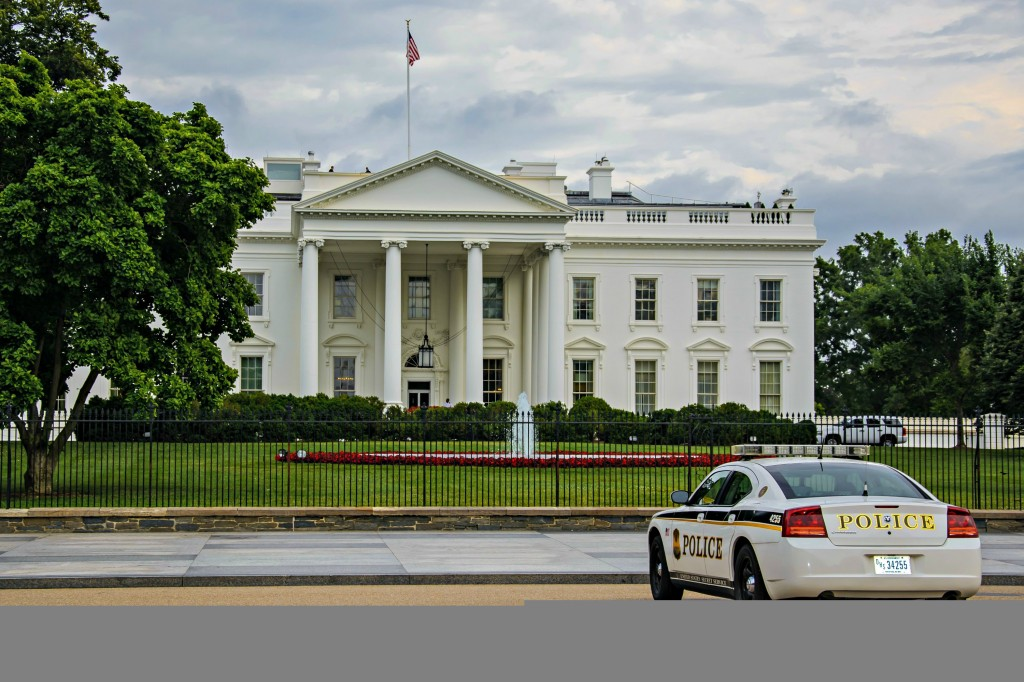 Secret Service in front of fence and on roof of White House.