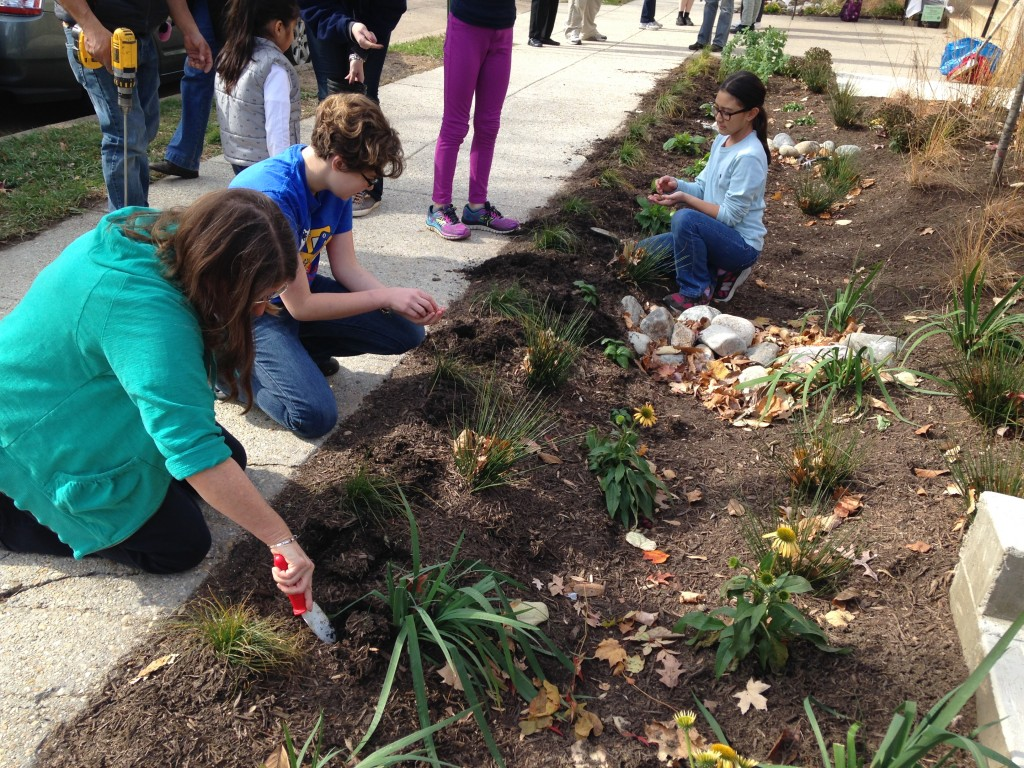 Tifereth Israel volunteers prepare the congregation's new rain garden for the planting of bulbs. Photo by Stan Dorn