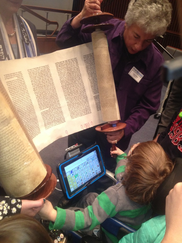 L.J. Seiff holds the Torah scroll as his grandmother Judy Seiff assists. Photo by Stephen Goldstein