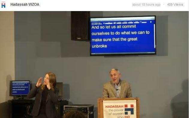 Hillel International's Eric Fingerhut speaks at Gallaudet University  as an interpreter signs.