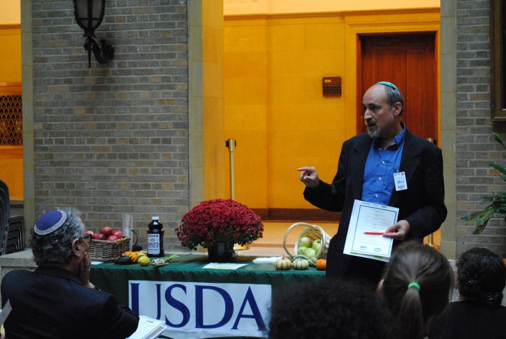 Rabbi Fred Scherlinder Dobb of Adat Shalom Reconstructionist Synagogue in Bethesda speaks at the USDA Sukkot celebration.