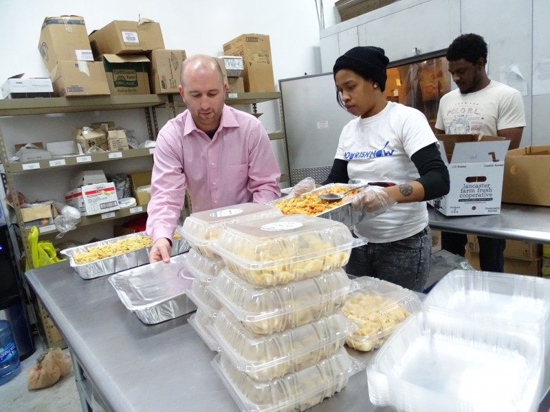 Brett Meyers, founder of Nourish Now, helps package hot meals. Photo by Suzanne Pollak