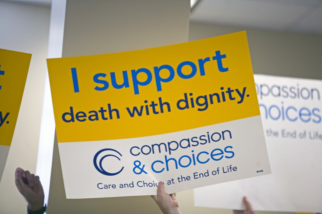 A sign carried by supporters of a bill that would allow terminally ill patients to choose to end their lives. Photo by Marc Shapiro