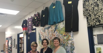 From left, Marcie Cissell, Barbara Frederick and Jodi Fishman of Bet Yeladim stand beneath some of the donated clothing