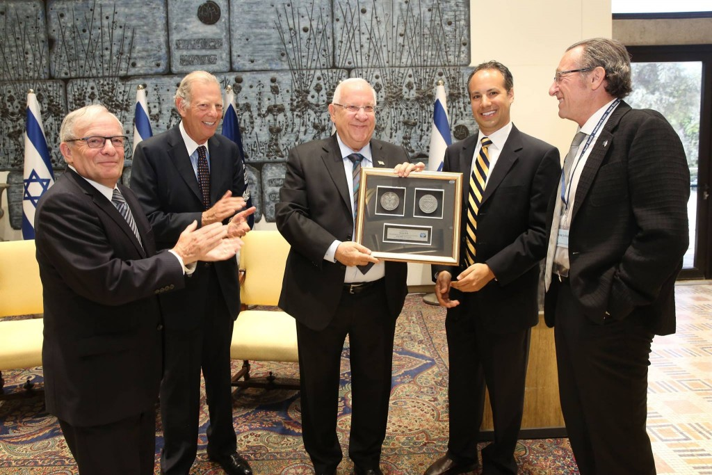 Israel Bonds President and CEO Izzy Tapoohi and Board Chairman Richard Hirsch applaud as Israeli President Reuven Rivlin is presented with the commemorative Bonds 65th anniversary medal by board member Jason Schwartz and international board member Jaime Schmidt Neuman Photo by Yossi Zamir.
