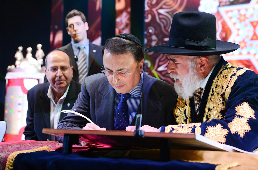 Lev Leviev, center, writes in a Torah scroll with Rabbi Eliyahu Yaakov, right, and Israel's then-defense minister, Moshe Ya'alon, in Jerusalem in 2014. Photo by Israel Barddougo/ World Congress of Bukhara Jews via JTA