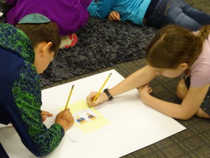 JPDS sixth-graders Isaac Trommer, left, and Adina Siff design their own political cartoon as part of the curriculum that is looking at political messaging. Photos by Daniel Schere