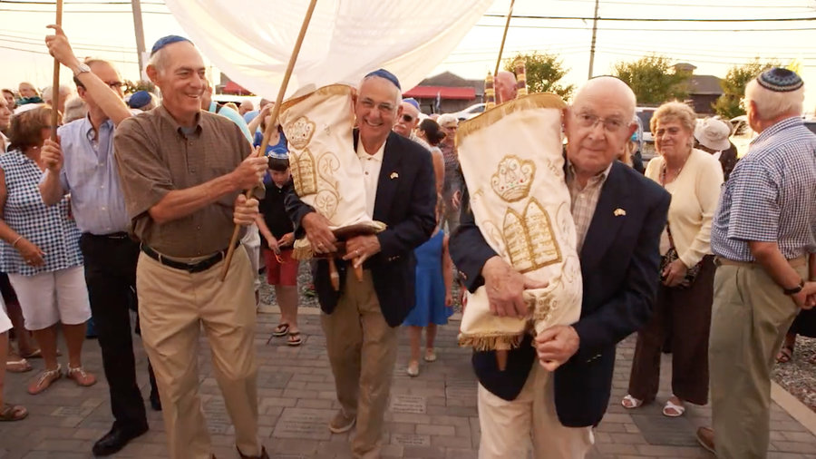 Mickey Radman, right, holds the Torah that served his Latrobe, Pa., congregation for so many years.  Photo courtesy 371 Productions