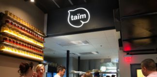 People stand in line at Taim counter
