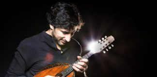 Man playing the mandolin in front of a black background.