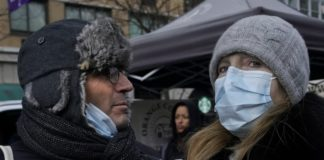 people in winter outwear wearing medical masks on the street