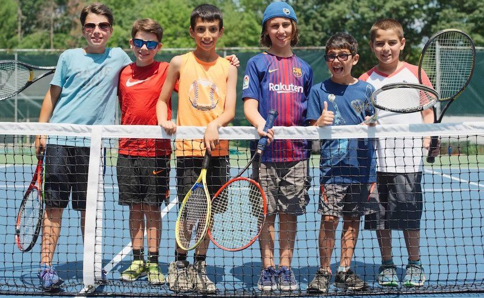 Kids holding tennis rackets on a tennis court