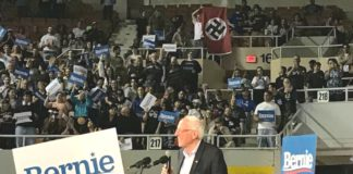 political rally for Democratic candidate Bernie Sanders, in foreground. man holding large Nazi flag in background.