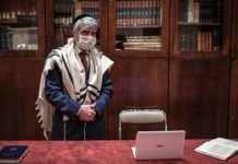 White-haired rabbi in prayer shawl, kippah, and surgical face mask stands in library by open laptop and prayerbook.