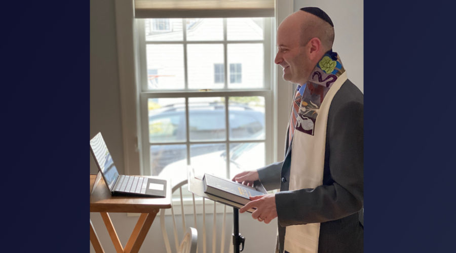 Bald man in colorful prayer shawl standing in profile reading from an open Torah scroll