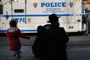 Silhouette of a man walking with a child and pushing a stroller in front of a NYPD police van