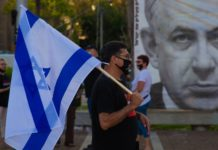 man wearing face mask marches with Israeli flag past a poster of Israeli Prime Minister Benjamin Netanyahu