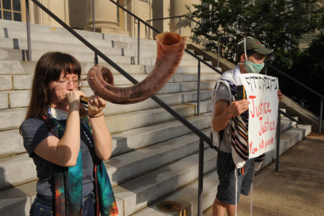 """Amanda Herring blows a shofar while her husband, Greg Herring, holds a sign that reads, """"Justice, justice shall you pursue."""" Photo by Lloyd Wolf"""