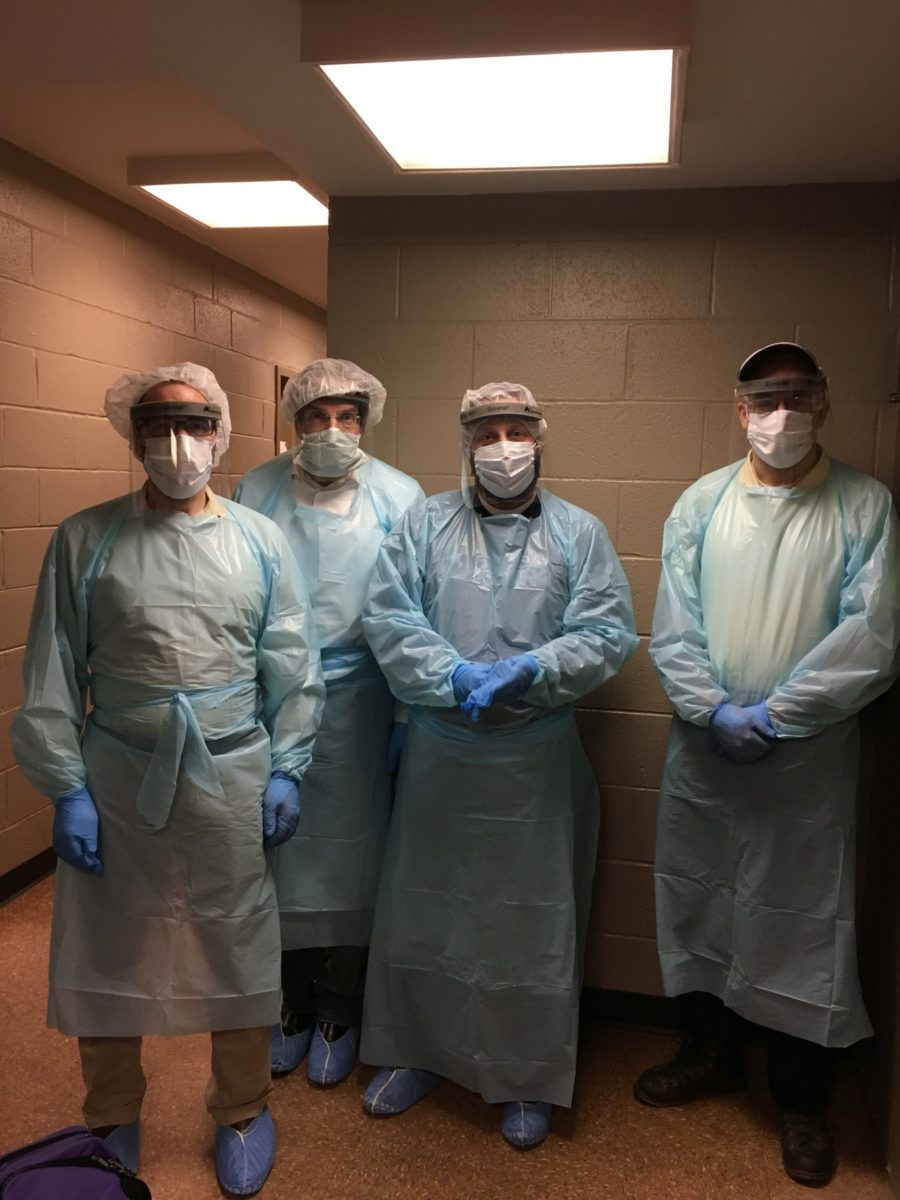 4 men in personal protective equipment including face masks, gowns, and gloves