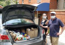 volunteers stand next to a car full of food