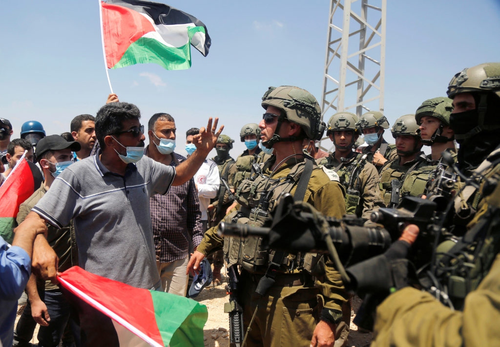 Palestinian demonstrators argue with Israeli forces
