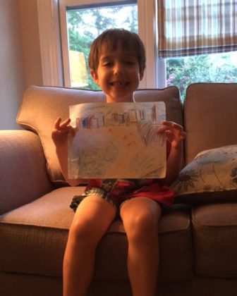 Second-grader Max Kander holds up a picture he drew of Tel Aviv.