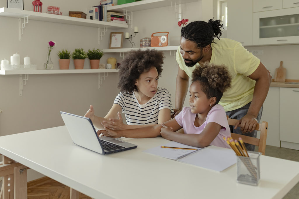 Two African American Parents Helping Their Daughter With Homework while using Laptop in the Kitchen at Home