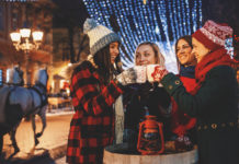 Group of friends enjoying the magic of Christmas by cheering with mulled wine and hot tea on a street at a city decorated with Christmas lights.