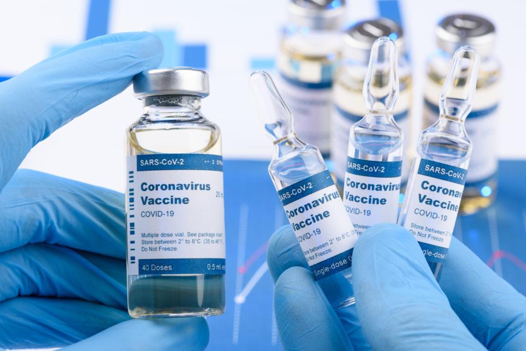 Coronavirus COVID-19 single dose small vials and multi dose in scientist hands concept. Research for new novel corona virus immunization drug. nevodka /