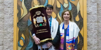 Steve and Karan Robinson hold the family Torah at its new home, Congregation Beth Emeth in Herndon.