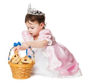 Little girl putting hamentashen in a purim basket.